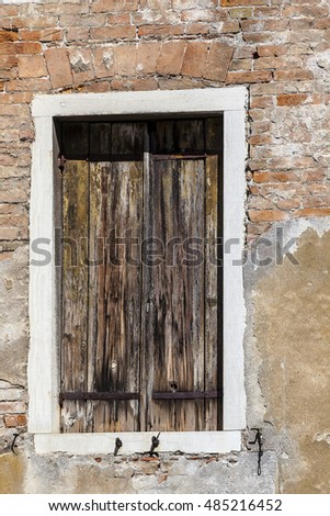 Close up on a old decrepit brick wall and window with closed wooden shutters, Sestier San Polo, Venice, Italy