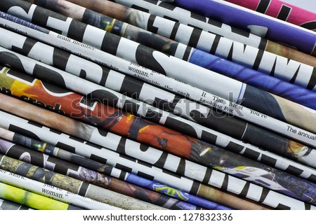 close up on a pile of differnt color newspaper titles - stock photo