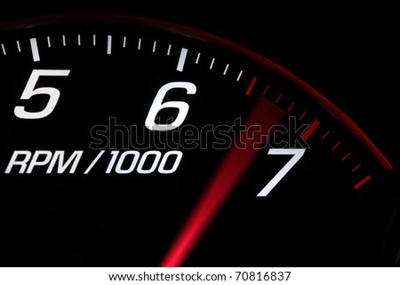 Close up on a tachometer reaching maximum engine speed - stock photo