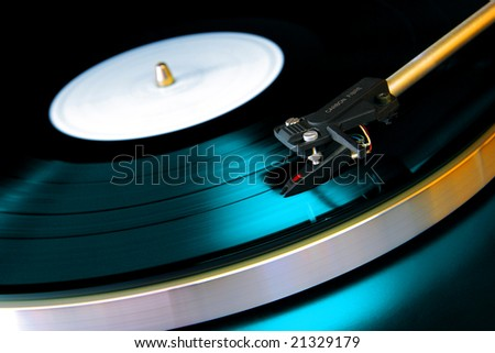 Close up on a vinyl record playing on a turntable - stock photo