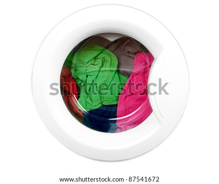 Close-up on a washing machine with clean colorful clothes - stock photo