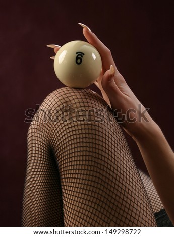 close-up on a woman's knee in a stocking clad ivory billiard ball on a burgundy background studio