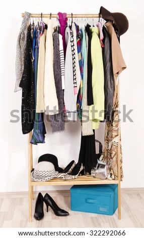 Close up on autumn winter clothes on hangers in a store. Colorful clothes and accessories hanging on a rack nicely arranged. - stock photo