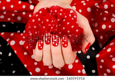 Close up on beautiful female hand with cute red manicure with white dots. Black and red dotted background. - stock photo