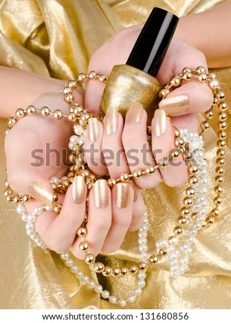 Close up on beautiful female hand with gold manicure. - stock photo