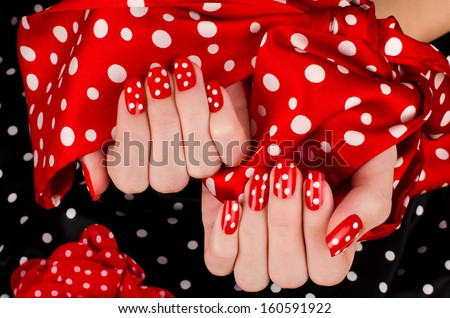 Close up on beautiful female hands with cute red manicure with white dots. Black dotted background. - stock photo