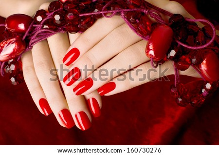 Close up on beautiful female hands with sexy red manicure. Red velvet background. - stock photo