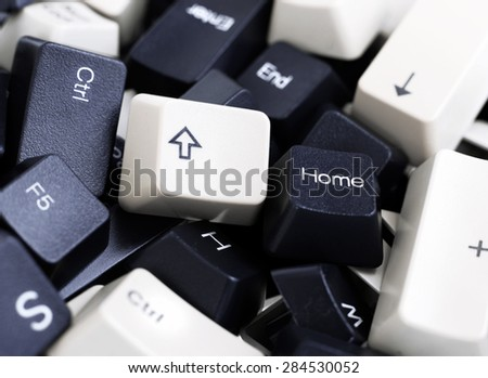 Close-up on Black and White Computer Keyboard Keys in a Pile. Home button and Up Arrow are in the focus - stock photo
