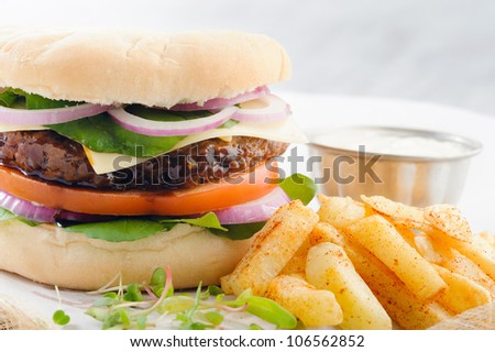 Close up on burger with thick beef patty, tomato, onion and lettuce with seasoned potato chips french fries - stock photo