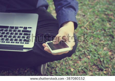 close up on business man work on smartphone and laptop at outdoor:man use electronics mobile notebook device equipment:people city lifestyle and technology concept.vintage tone retro film effect image - stock photo