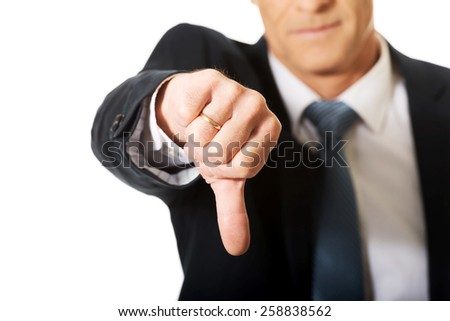 Close up on businessman hand showing thumb down sign. - stock photo
