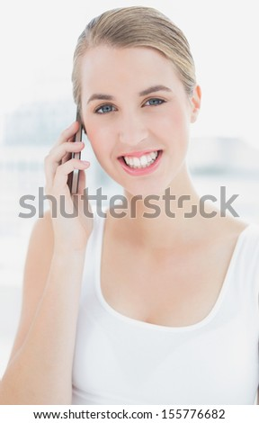 Close up on cheerful sporty woman in bright sports hall having a phone call - stock photo