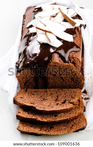 Close up on chocolate cake with chocolate frosting flowing down the side, garnished with coconut slices - stock photo