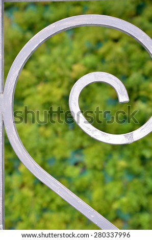 Close up on curves railing. Grey color on green background.