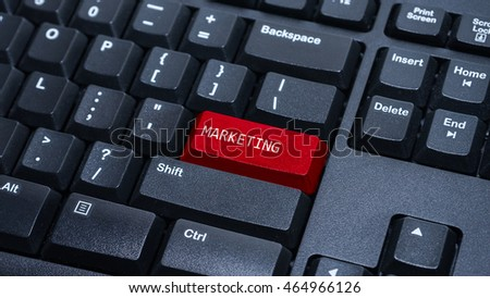 Close up on customized computer enter button on keyboard with a word marketing.