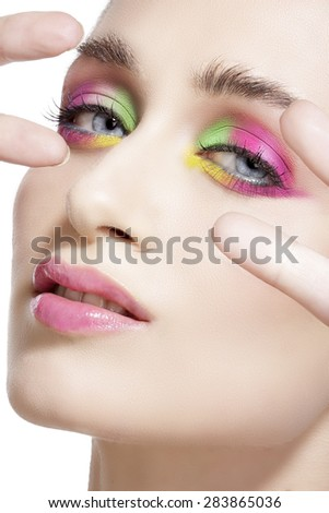 Close up on eyes , making colorful eyeshadows and eyeliner on white