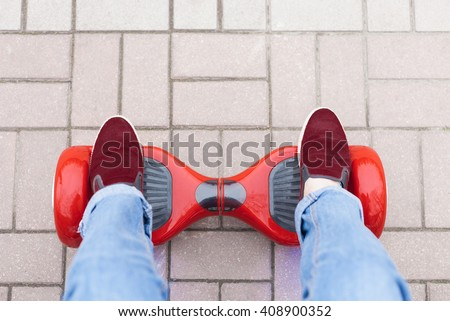 Close up on feet of a girl in marsala shoes riding on a modern red electric mini segway or hover board scooter. Trending new transportation technology that produces no air pollution to the atmosphere. - stock photo