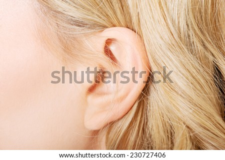 Close up on female ear. - stock photo
