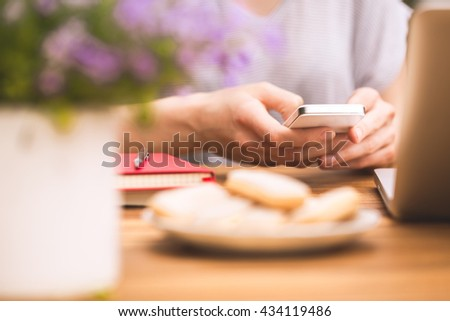 Close-up on female hands holding smartphone and writing text message in the coffee shop. Relax and joy.