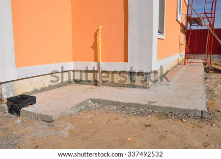 Close up on foundation wall  waterproofing, drainage, gas pipe, colorful facade . Properly insulated basement wall can save you money on heating and provide a dry, comfortable living space. - stock photo