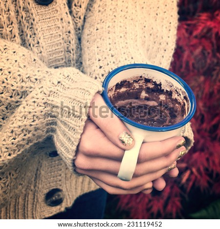 Close-up on girl hands with sweater holding a hot chocolate, vintage process - stock photo