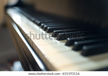 Close up on grand piano keyboard with depth of field blurry effect in the background