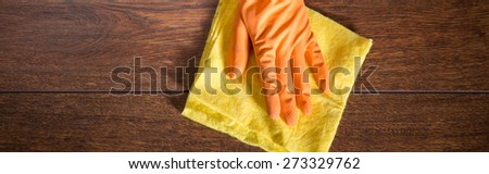 Close-up on hand in glove cleaning wooden parquet - stock photo