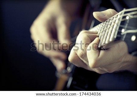 Close up on hands playing on electric guitar  - stock photo