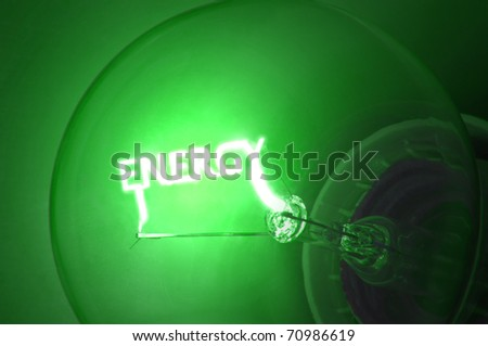 "Close up on illuminated green light bulb filament which spells the word ""ENERGY"". - stock photo"