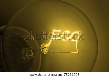 """Close up on illuminated yellow light bulb filament spelling the word """"Eco"""". - stock photo"""