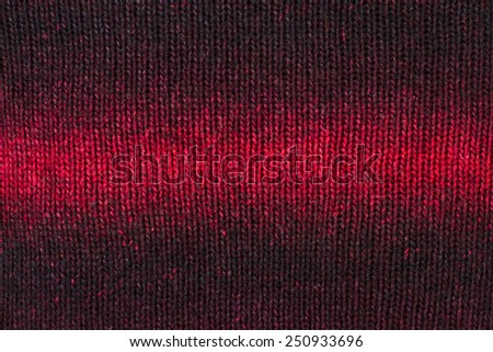 Close up on knit woolen texture. Ombre red woven thread sweater as a background. - stock photo