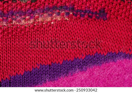 Close up on knit woolen texture. Pink, purple and red woven thread sweater as a background. - stock photo
