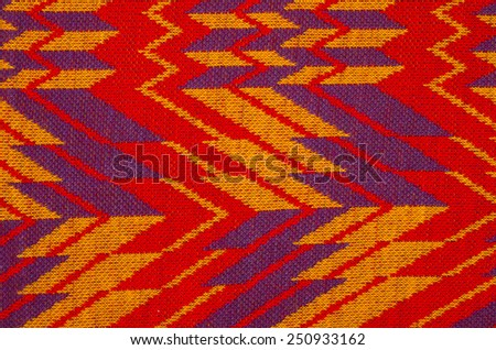 Close up on knit woolen texture. Red and purple retro woven thread as a background. - stock photo