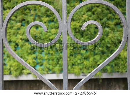 Close up on love heart shape railing. Railing of the shape of a heart with elegant curves. Dark grey color on green background. - stock photo