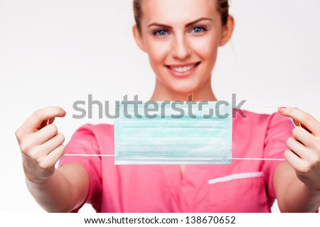 close-up on medical mouth protection with smiling nurse - stock photo