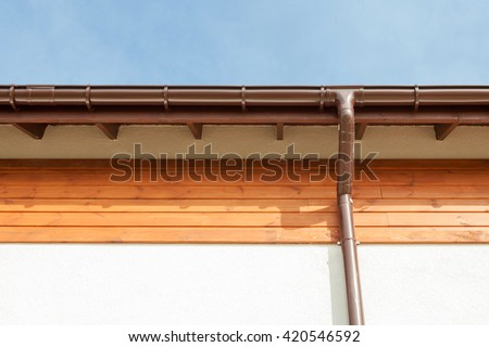 Close up on New Rain Gutter, Downspout, Soffit Board, Fascia Board Installation Against Blue Sky - stock photo