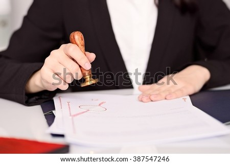 Close up on Notary Public woman hands stamping notary act . Law office concept.