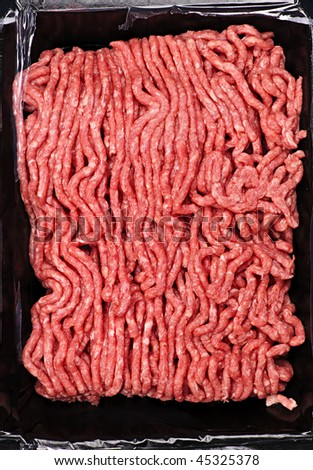 Close up on package of lean red raw ground meat - stock photo