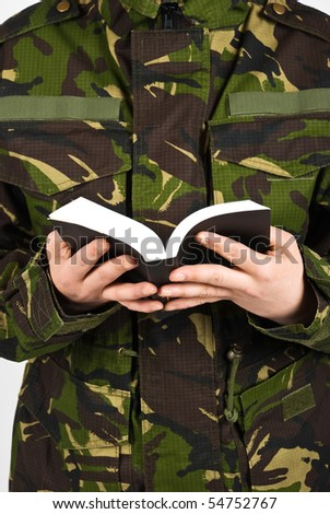Close up on part body of army soldier  reading a bible - stock photo