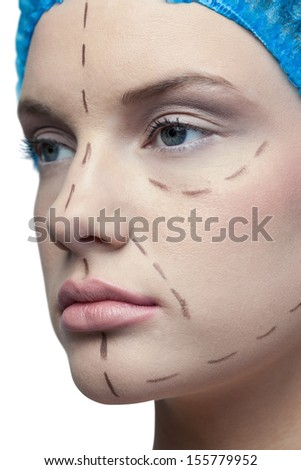 Close up on peaceful young patient with dotted lines on the face before surgery