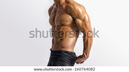 Close up on perfect abs. Strong bodybuilder with six pack.Strong bodybuilder man with perfect abs, shoulders,biceps, triceps and chest, personal fitness trainer flexing his muscles - stock photo