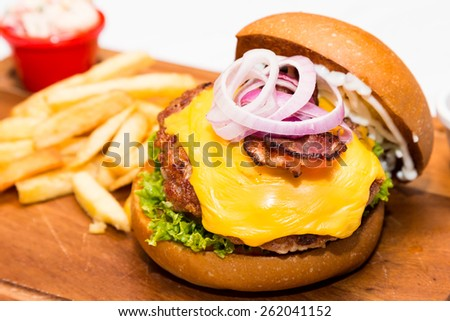 Close up on Pork burger with cheese, vegetable and served with fries - stock photo