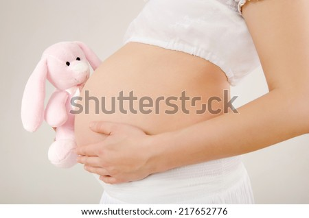 Close up on pregnant belly with toy. Woman expecting a baby with a cute pink rabbit toy peaking at her belly. Easter baby. - stock photo