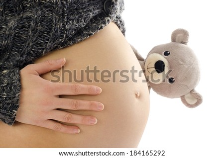 Close up on pregnant belly. Woman expecting a baby with a cute teddy bear peaking at her belly. - stock photo