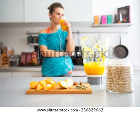 Close-up on pumpkin smoothie and ingredients on table and fitness young woman in background - stock photo