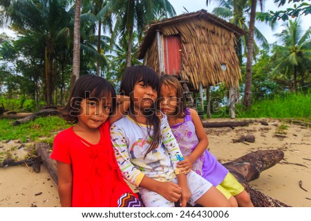 Close up on Sea Bajau children posing in front of their traditional house. Shallow dof, selective focus on the face of the children. - stock photo