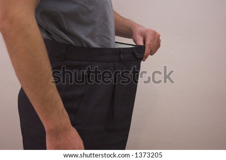 Close up on slimmed down male waistline wearing old trousers to demonstrate weight loss. - stock photo