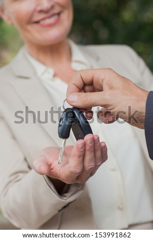 Close up on smiling businesswoman being given keys by her partner