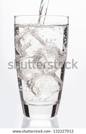Close up on sparkling water filling a glass on white background - stock photo