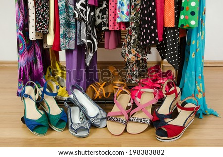 Close up on summer sandals in a wardrobe. Dressing closet with colorful clothes and shoes nicely arranged. - stock photo